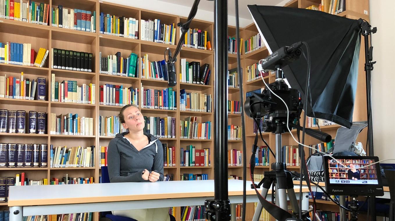 Eine Frau sitzt an einem Tisch. Sie spricht in eine Kamera. Gleichzeitig ist eine Kamera und ein Scheinwerfer auf Sie gerichtet.