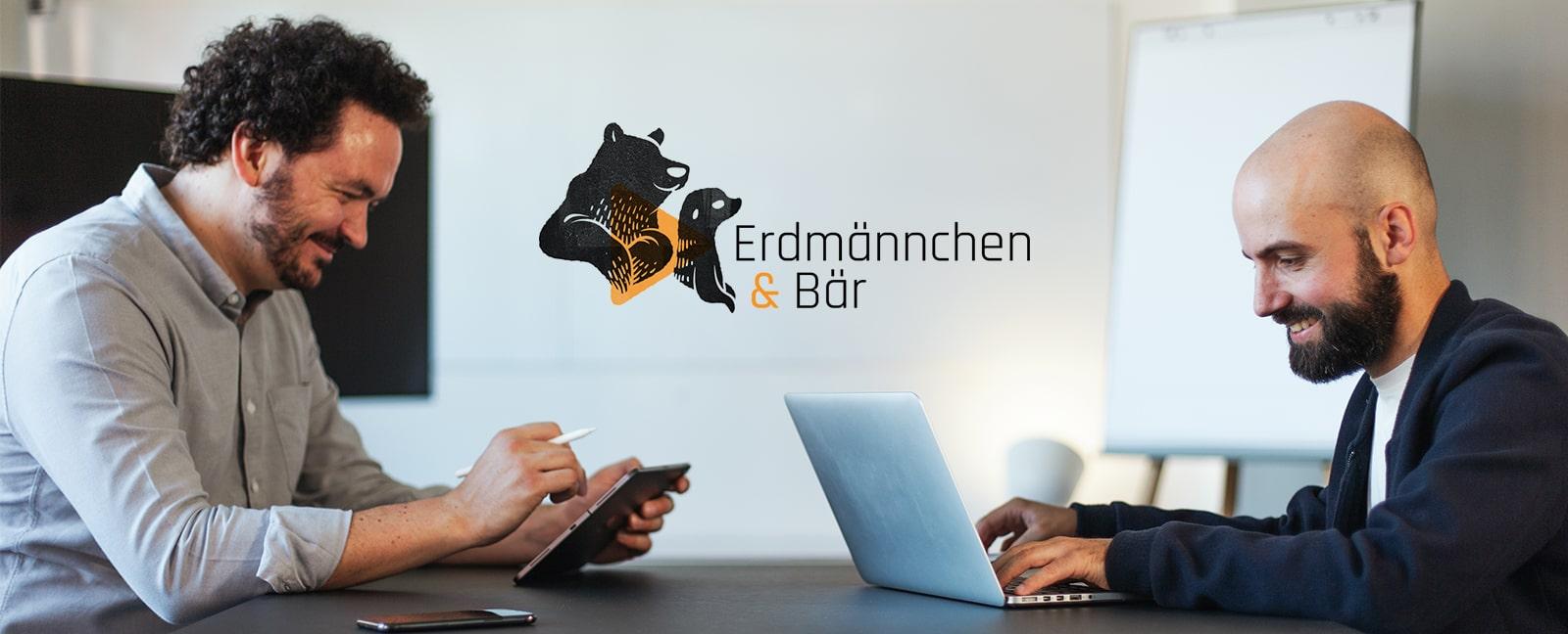 2 Männer sitzen an einem Tisch. Links ist Sebastian zu sehen und rechts Felix. Beide lachen und schauen auf ihre Arbeitsgeräte. In der Mitte ist das Logo von Erdmännchen&Bär